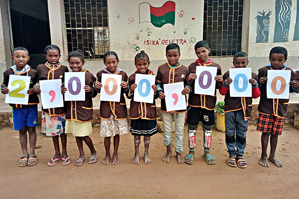 Schulkinder aus Madagaskar halten Schilder in der Hand, die zusammen die Zahl 2 Millionen bilden